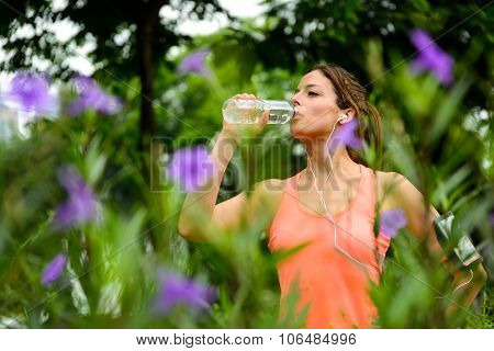 Female Athlete Drinking Water During Running Rest