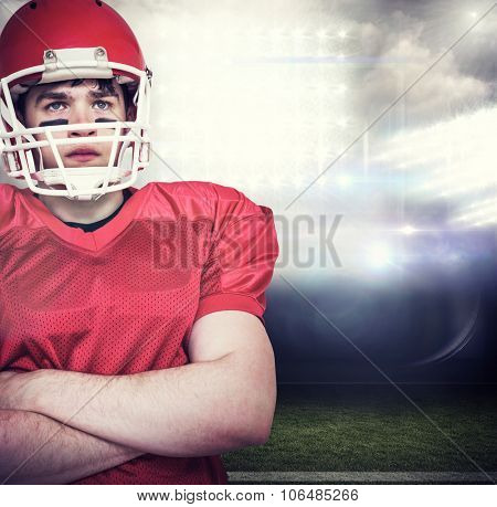 American football player with arms crossed against sports pitch