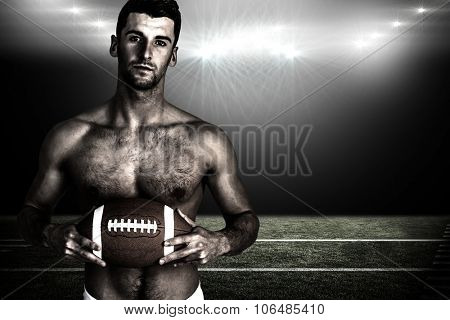Portrait of shirtless rugby player with the ball against spotlight