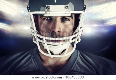 American football player looking at camera against sports pitch