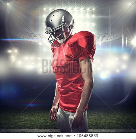 American football player in red jersey looking down against american football arena