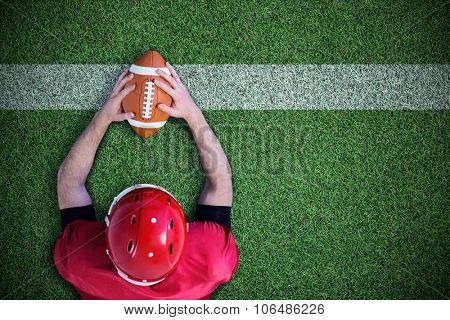 American football player reaching football against pitch with line