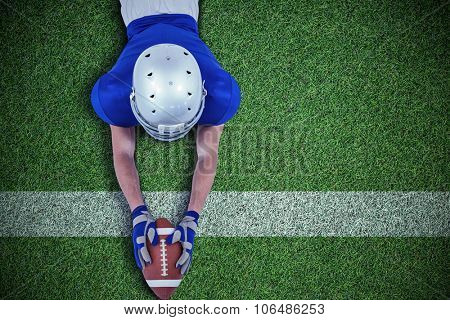 High angle view of American football player reaching towards ball against pitch with line