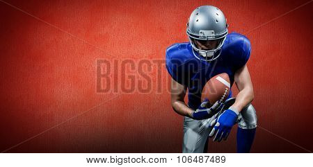 American football player holding ball while kneeling against red background