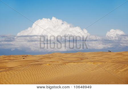 A lonely figure of a man and a motorbike in the desert