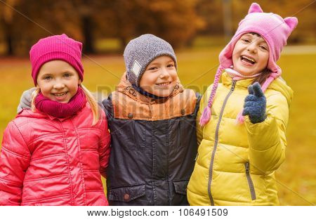 childhood, leisure, friendship and people concept - group of happy kids hugging and pointing finger on you in autumn park