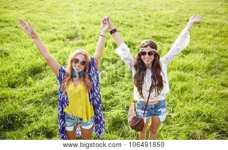 nature, summer, youth culture, friendship and people concept - smiling young hippie women dancing on green field
