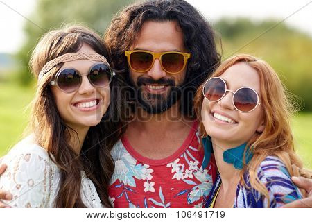 nature, summer, youth culture and people concept - smiling young hippie friends in sunglasses outdoors