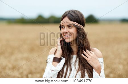 nature, summer, youth culture and people concept - smiling young hippie woman on cereal field