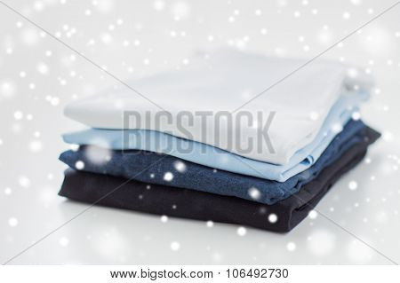 ironing, laundry, clothes, housekeeping and objects concept - close up of ironed and folded t-shirts on table at home over snow effect