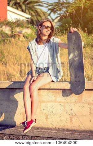 Young girl with skateboard sitting over the wall on summer