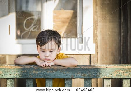 Melancholy Mixed Race Boy Leaning on Porch Railing.