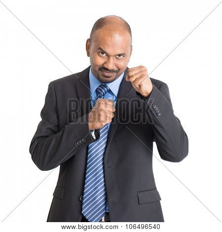 Mature Indian businessman in kungfu fighting mood, standing on plain background with shadow.