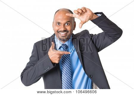 Cheerful Indian businessman making fingers frame and peeping through, on plain background