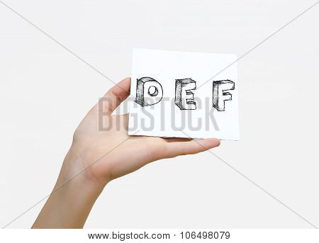 Hand Holding A Piece Of Paper With Sketchy Capital Letters  D E F, Isolated On White.