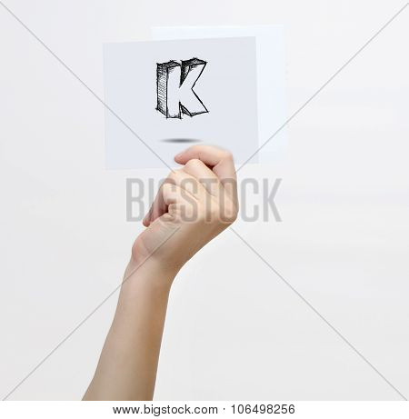 Hand Holding A Piece Of Paper With Sketchy Capital Letter K, Isolated On White.