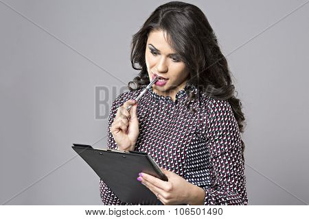 Portrait Of A Young Female Entrepreneur Thinking While Taking Notes