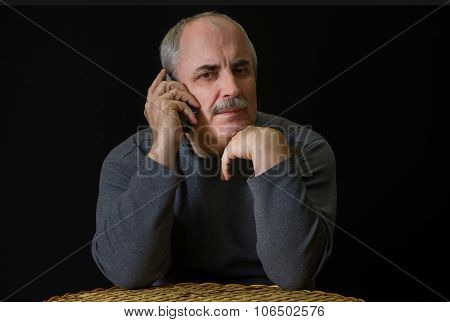 mature Caucasian man listening cellular phone