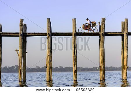 MANDALAY, MYANMAR - OCTOBER 26, 2015: A cyclist pushes his bike across the U Bein Bridge. The bridge was built around 1850 and is the oldest and longest teakwood bridge in the world.