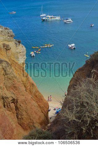 Beach at the bottom of sea cliffs Lagos Portugal.
