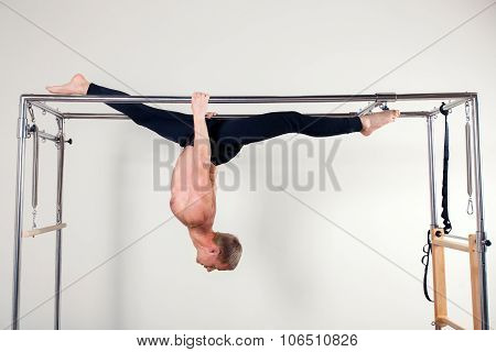 Pilates aerobic instructor man in cadillac fitness exercise acrobatic upside down balance