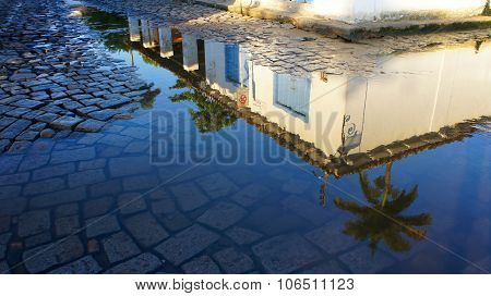 Reflection Of A Colonial House On A Water Puddle In Paraty, Brazil.