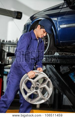 Young male mechanic holding metallic alloy at auto repair shop