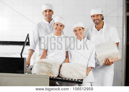 Portrait of confident male and female Baker's with packed breads in bakery