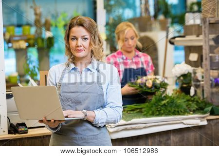 Portrait of female florist using laptop with colleague working in background at flower shop