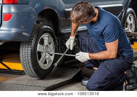 Male mechanic fixing car tire with rim wrench at garage