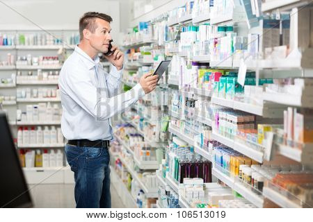 Mid adult male customer using mobile phone and digital tablet while looking at products in pharmacy