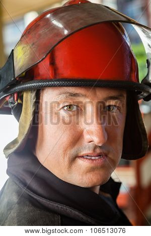 Closeup portrait of confident firefighter wearing red helmet at fire station
