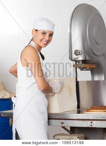 Portrait of happy young baker using bread cutting machine in bakery