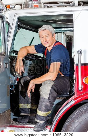 Portrait of smiling male firefighter sitting in truck at fire station