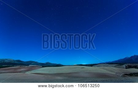 Nighttime View Over Fields To Mountains At Night