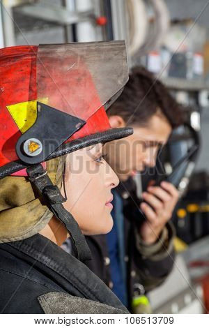 Side view of female firefighter at fire station with male colleague in background