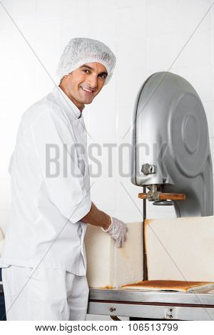 Portrait of smiling male baker with bread loaf standing at cutting machine in bakery