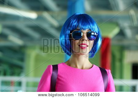 Portrait of young woman with blue hairstyle, indoors