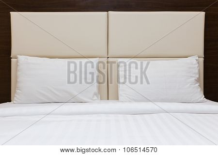 Bedroom With White Pillow And Leather Headboard