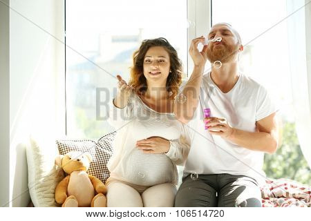 Happy beloved man and pregnant woman blow soap bubbles in waiting for baby's birth on window board