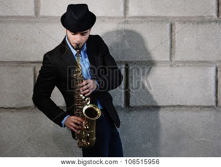 Elegant young man with sax on brick wall background