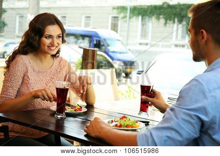 young couple flirting on cafe's summer terrace