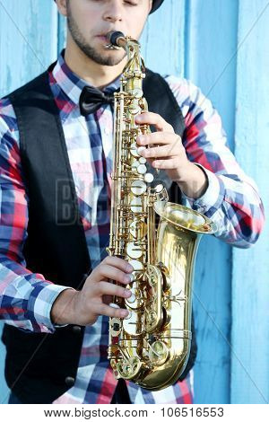 Handsome man in hat plays sax on blue wooden background, close up