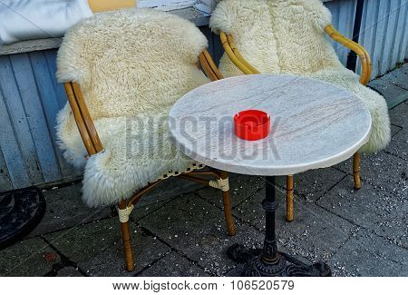 Couple Of Wicker Chairs Covered With Sheepskin