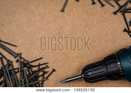 Screwdriver and screws on the wood plate