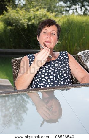 Attractive Woman Is Looking Sceptical On  E-cigarette In Garden