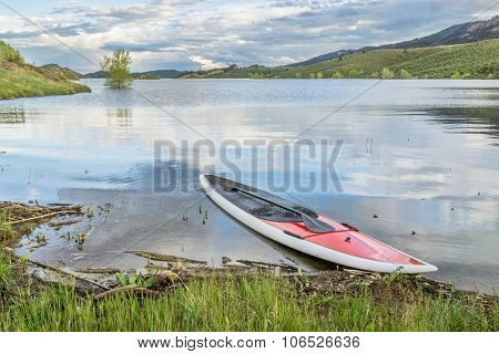 red SUP paddleboard with a paddle on a grassy lake shore - Horsetooth Reservoir near Fort Collins, Colorado