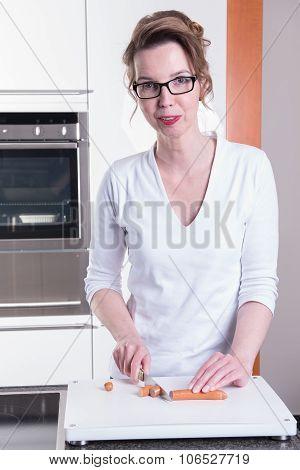 Attractive Woman In Modern Ktchen Cutting Sausage