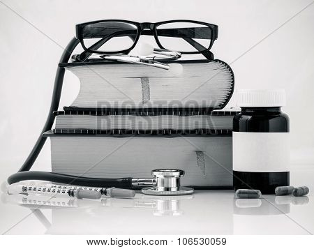 Stethoscope On A Textbooks And Bottle Of Pills Isolated On White Background.