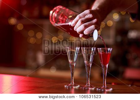 Barman Pouring Red Shots